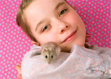Girl (7-9) holding pet hamster, smiling, portrait, close-up Stock Photo - Premium Royalty-Free, Code: 6106-06981689