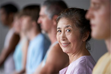 People in yoga class (focus on senior woman smiling) Stock Photo - Premium Royalty-Free, Code: 6106-06981903