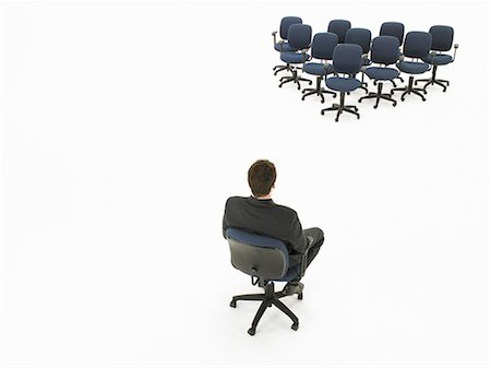 descriptive - Businessman facing empty office chairs forming triangle, elevated view Stock Photo - Premium Royalty-Free, Code: 6106-06982561