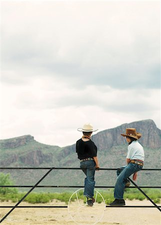 Two young boys (7-10) sitting on ranch fence Stock Photo - Premium Royalty-Free, Code: 6106-06982751