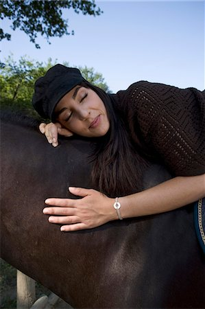 Young woman lying on horse, eyes closed Stock Photo - Premium Royalty-Free, Code: 6106-06982829