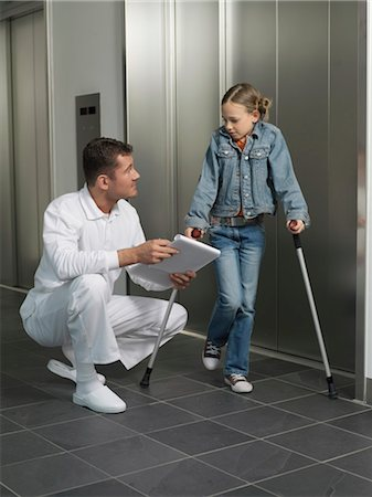 Doctor squatting by girl (7-10) on crutches Stock Photo - Premium Royalty-Free, Code: 6106-06983383