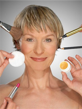 Mature woman surrounded by make-up equipment, portrait Stock Photo - Premium Royalty-Free, Code: 6106-06983332