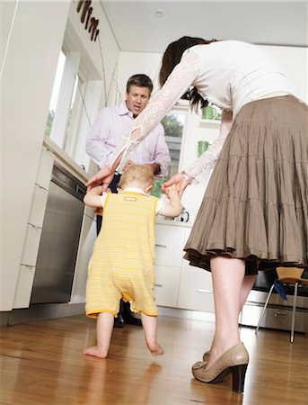 Mother helping daughter (9-12 months) walking towards father in kitchen Stock Photo - Premium Royalty-Free, Code: 6106-06983802