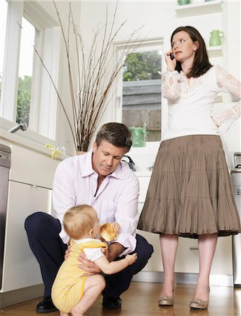Father crouching at daughter (9-12 months) mother standing in kitchen Stock Photo - Premium Royalty-Free, Code: 6106-06983805