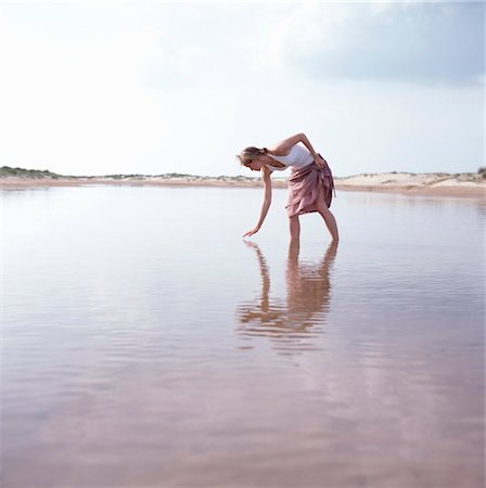 Young woman wading in water Stock Photo - Premium Royalty-Free, Code: 6106-06984329