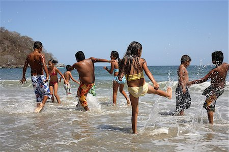 preteen girl wet clothes - Children (5-10) playing and splashing in sea Stock Photo - Premium Royalty-Free, Code: 6106-06984644