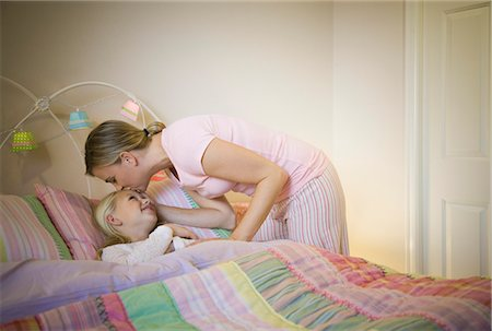 daughter kissing mother - Mother kissing daughter (8-9) goodnight in bed Stock Photo - Premium Royalty-Free, Code: 6106-06985632