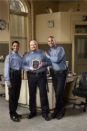 female police officer happy - Three police officers, one holding award, portrait Stock Photo - Premium Royalty-Free, Code: 6106-06986804