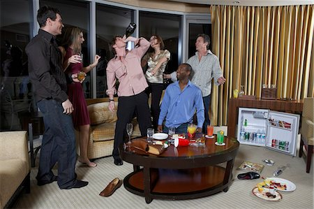 Group of people celebrating in hotel room, teenage boy (16-17) drinking from wine bottle Stock Photo - Premium Royalty-Free, Code: 6106-06988832