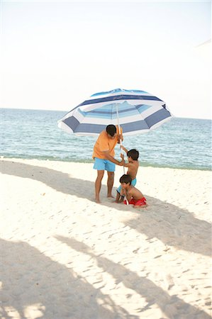 father son shirtless - Father and two sons (6-7) setting up umbrella in sand on beach Stock Photo - Premium Royalty-Free, Code: 6106-06989236