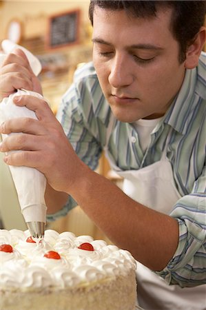 descriptive - Young man wearing apron, putting whipped cream on cake Stock Photo - Premium Royalty-Free, Code: 6106-06989960