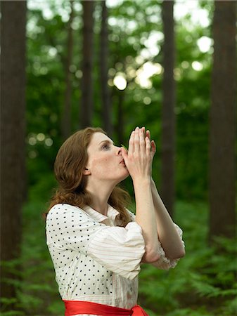 Woman in forest, holding blade of grass to lips and blowing Stock Photo - Premium Royalty-Free, Code: 6106-06990068