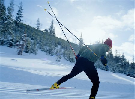 Young man cross-country skiing, rear view Stock Photo - Premium Royalty-Free, Code: 6106-06992609