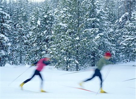 Young man and woman cross-country skiing, side view (blurred motion) Stock Photo - Premium Royalty-Free, Code: 6106-06992610