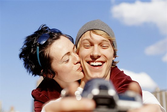 Young couple taking self portrait, woman kissing man Stock Photo - Premium Royalty-Free, Image code: 6106-06992771
