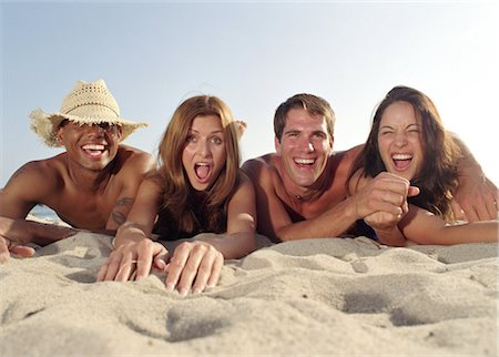 Two young couples lying on beach, portrait, close-up Stock Photo - Premium Royalty-Free, Code: 6106-06993354