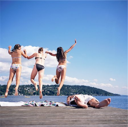 Teenage girls (14-16) holding hands, jumping into lake, rear view Stock Photo - Premium Royalty-Free, Code: 6106-06993589