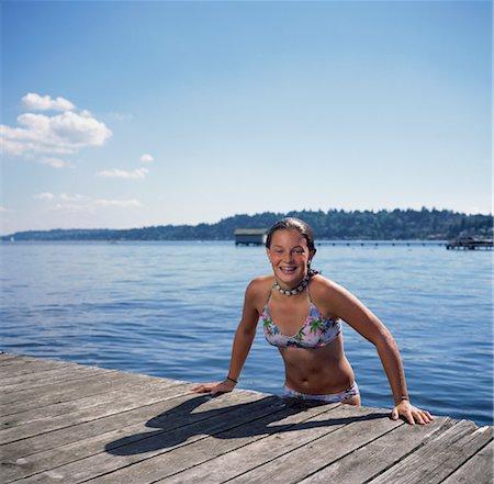 Teen girl (14-16) climbing out of lake onto dock Stock Photo - Premium Royalty-Free, Code: 6106-06993590