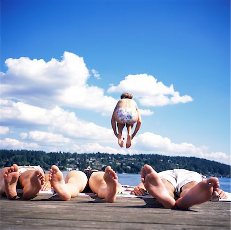 Teenagers (14-16) lying on dock, girl jumping into lake, rear view Stock Photo - Premium Royalty-Free, Code: 6106-06993592