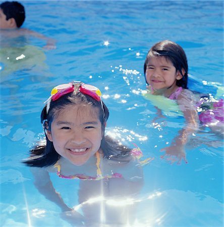 preteen girl wet clothes - Two sisters (4-7) playing in swimming pool, smiling Stock Photo - Premium Royalty-Free, Code: 6106-06993761
