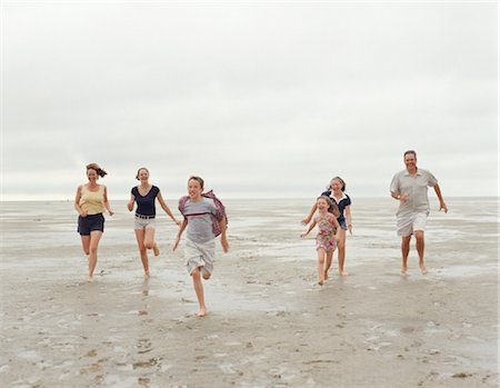 preteen girl wet clothes - Family running on beach, Cape Cod, USA Stock Photo - Premium Royalty-Free, Code: 6106-06994566