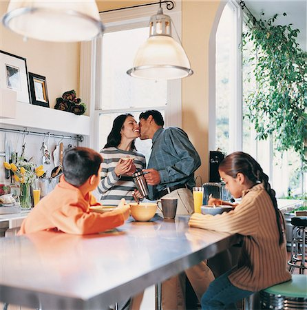 daughter kissing mother - Family in a Kitchen in the Morning Stock Photo - Premium Royalty-Free, Code: 6106-06995773