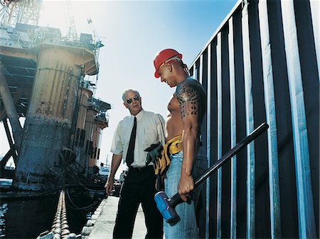 sweaty businessman - Businessman Talking to a Docker by an Oil Rig at the Water's Edge Stock Photo - Premium Royalty-Free, Code: 6106-06996164