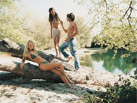 Young Couple Holding Hands Standing on a Log and a Serious Excluded Woman Lying Looking at the Camera Stock Photo - Premium Royalty-Free, Code: 6106-06999126