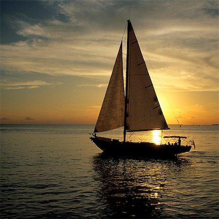 sailboat  ocean - A sailboat in golden light at sunset, Miami Beach Stock Photo - Premium Royalty-Free, Code: 6106-07069927