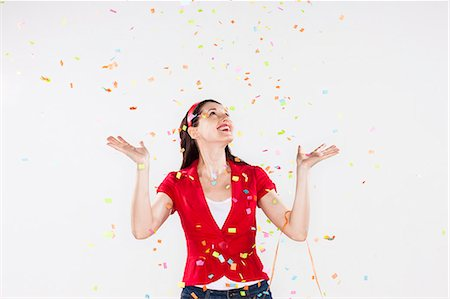 young woman with confetti falling around her Stock Photo - Premium Royalty-Free, Code: 6106-07070168