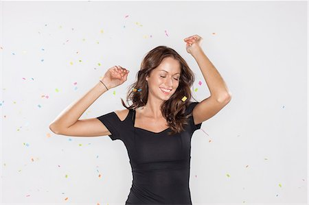 Portrait of Beautiful young woman confetti Stock Photo - Premium Royalty-Free, Code: 6106-07070193