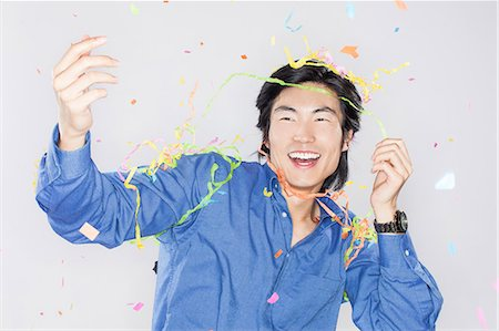 Portrait of young man with confetti Stock Photo - Premium Royalty-Free, Code: 6106-07070241