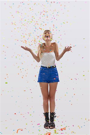 young woman with confetti flying Stock Photo - Premium Royalty-Free, Code: 6106-07070217