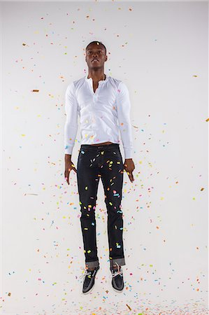 falling confetti with white background - Young man jumping, confetti floating around him Stock Photo - Premium Royalty-Free, Code: 6106-07070234