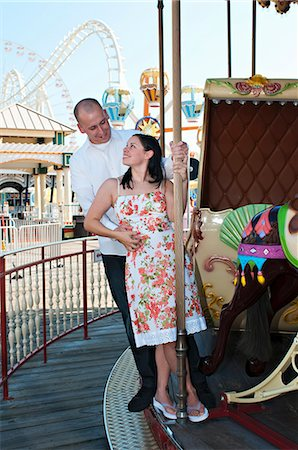 Young engaged couple on a carousel. Stock Photo - Premium Royalty-Free, Code: 6106-07070510