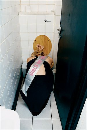 Rear View of a Young Woman Vomiting and Crouching in Front of a Lavatory Stock Photo - Premium Royalty-Free, Code: 6106-07002312