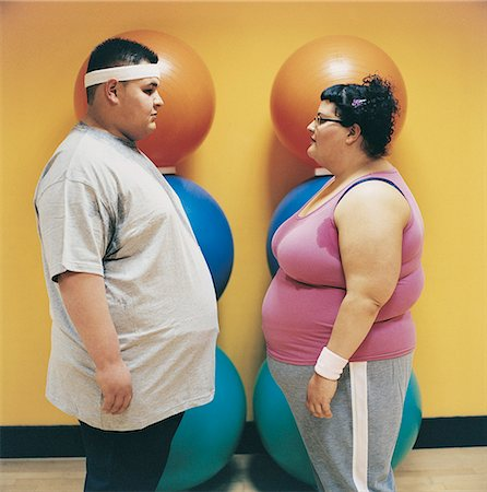 fat man exercising - Overweight Man and Woman Standing Face to Face in a Gym Stock Photo - Premium Royalty-Free, Code: 6106-07002441