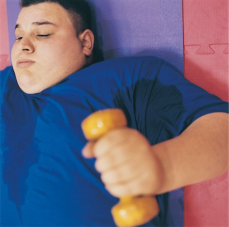 fat man exercising - Young Man Lying on an Exercise Mat Lifting a Dumbbell Stock Photo - Premium Royalty-Free, Code: 6106-07002449