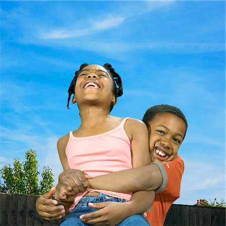 Brother Lifting His Sister as They Play Together Outside Stock Photo - Premium Royalty-Free, Code: 6106-07004056