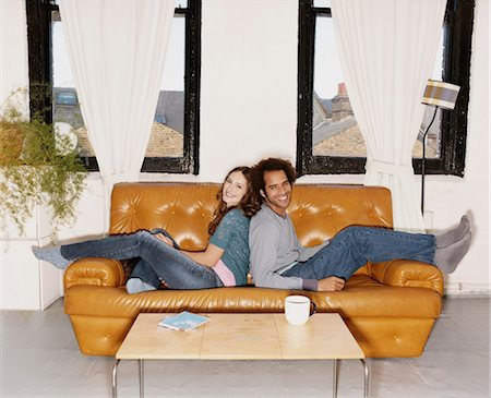 Portrait of a Couple Sitting Back to Back on a Leather Sofa Stock Photo - Premium Royalty-Free, Code: 6106-07005830