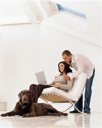Woman Using a Laptop Computer with a Man Standing Behind her and a Pet Dog Sitting on the Floor Stock Photo - Premium Royalty-Free, Code: 6106-07006248
