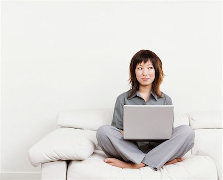 female white background full body - Woman Sitting Cross-legged on a White Sofa, Looking Sideways and Using a Laptop Computer Stock Photo - Premium Royalty-Free, Code: 6106-07006566