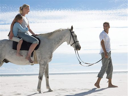 Man Leads a Horse With His Wife and Daughter Along the Beach Stock Photo - Premium Royalty-Free, Code: 6106-07009600