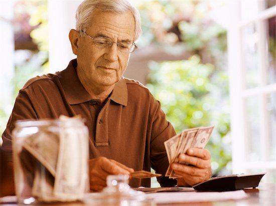 Senior Man Sitting at a Table Counting Dollar Bills Stock Photo - Premium Royalty-Free, Image code: 6106-07010144