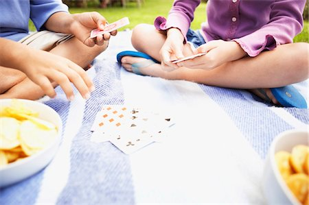 preteen thong - Low Section of a Young Boy and Girl Sitting on a Rug, Playing a Card Game Stock Photo - Premium Royalty-Free, Code: 6106-07010341