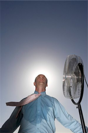 sweaty businessman - Low Angle View of a Sweaty Businessman Standing Next to an Electric Fan Stock Photo - Premium Royalty-Free, Code: 6106-07010987