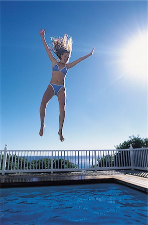 Woman jumping into a swimming pool Stock Photo - Premium Royalty-Free, Code: 6106-07012655