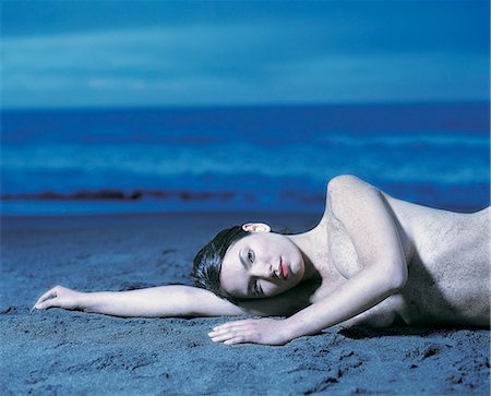 Naked Woman Lying on the Beach Stock Photo - Premium Royalty-Free, Code: 6106-07015191