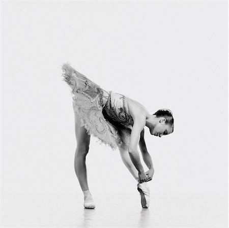 Female Ballerina Bending Over to Tie Her Ballet Shoe Stock Photo - Premium Royalty-Free, Code: 6106-07019215